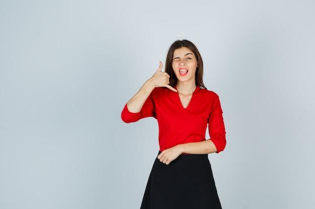 Giovane donna in camicetta rossa, gonna nera che mostra il gesto del telefono