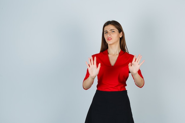 Young woman in red blouse, black skirt showing restriction gesture and looking displeased