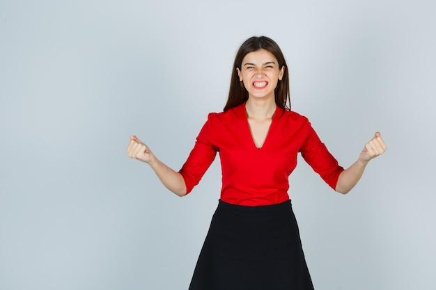 Young woman in red blouse, black skirt showing winner gesture and looking happy