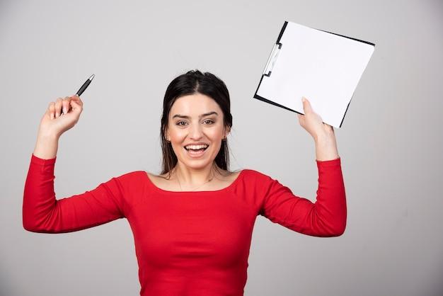 Giovane donna in camicetta rossa con appunti felice.