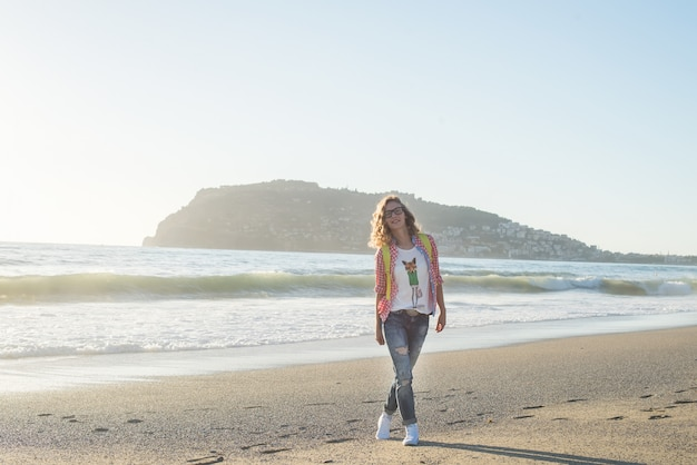 Young woman in red checkered shirt, jeans, white sneakers walking along beach and the stormy ocean on sunny winter day