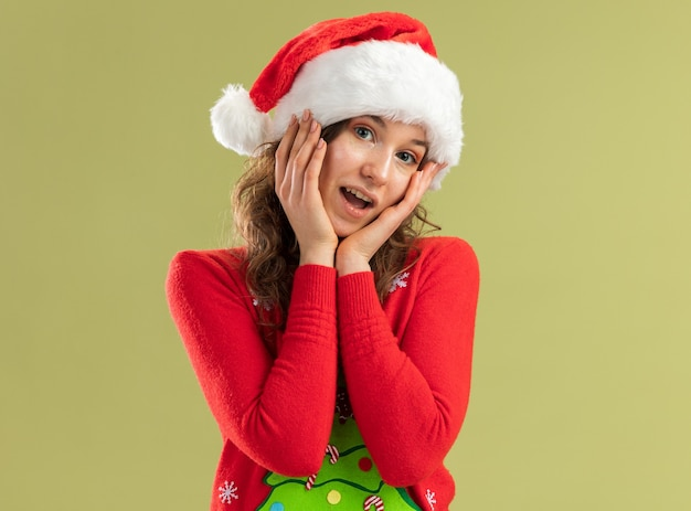 Giovane donna in maglione rosso di natale e cappello della santa che sembrano sorridere felice e positivo