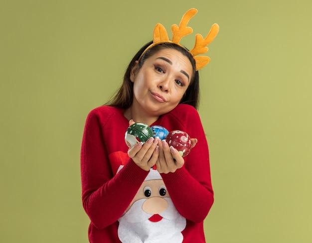 Giovane donna in maglione rosso di natale che indossa orlo divertente con le corna dei cervi che tengono le palle di natale che sembrano sorridere confuso