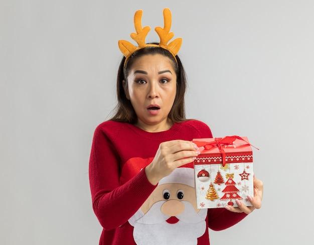 Giovane donna in maglione rosso di natale che indossa l'orlo divertente con le corna dei cervi che tengono il regalo di natale che sembra essere sorpreso