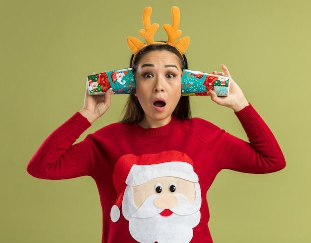 Giovane donna in maglione rosso di natale che indossa un bordo divertente con corna di cervo che tiene bicchieri di carta colorati sopra l'orecchio cercando di ascoltare qualcosa dentro che sembra sorpreso in piedi sul muro verde