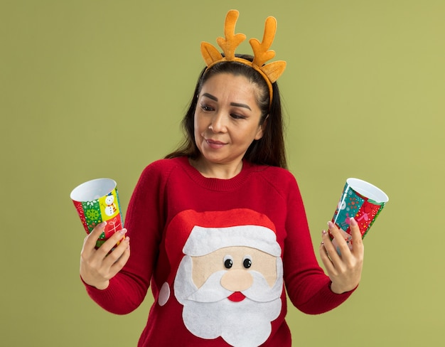 Young woman in  red christmas sweater wearing funny rim with deer horns holding colorful paper cups looking confused trying to make choice  standing over green wall