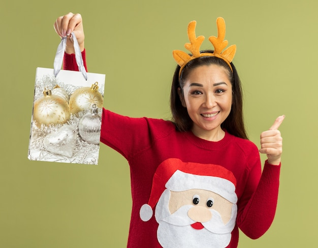 Young woman in  red christmas sweater wearing funny rim with deer horns  holding paper bag with christmas gift  with smile on face showing thumbs up standing over green wall