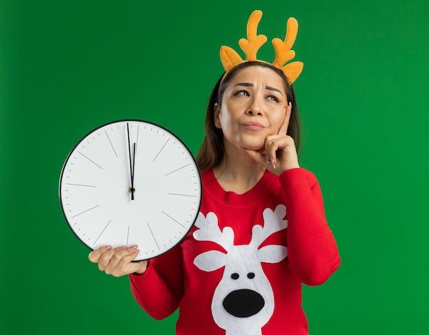 Giovane donna in maglione rosso di natale che indossa il bordo divertente con le corna dei cervi che tengono l'orologio di parete che osserva in su in piedi perplesso sopra fondo verde