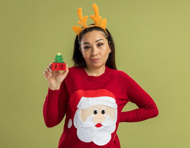 Young woman in  red christmas sweater wearing funny rim with deer horns   showing toy cubes with date twenty five  with skeptic smile  standing over green wall