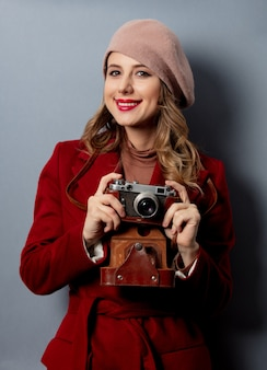 Young woman in red coat with photo camera