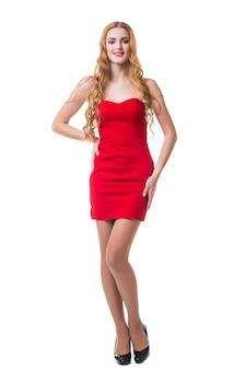 Giovane donna in abito rosso ballando su sfondo bianco