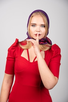 Young woman in red dress giving silent treatment.