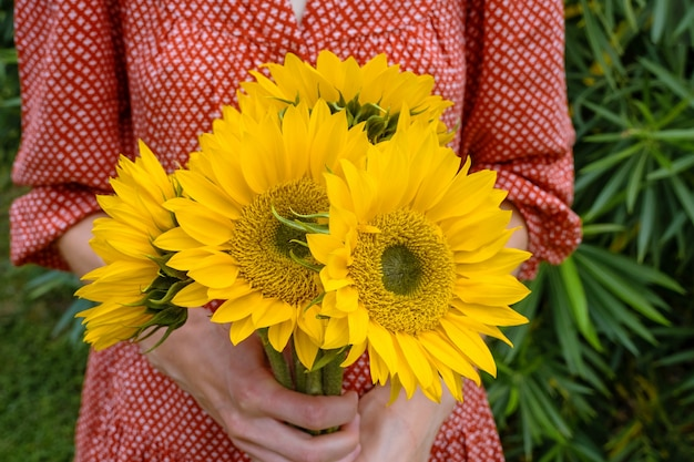 Young woman in red dress holding a large bouquet of sunflowers.