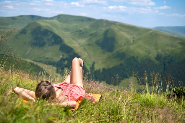 Young woman in red dress lying down on green grassy field resting on a sunny day in summer mountains enjoying view of nature.
