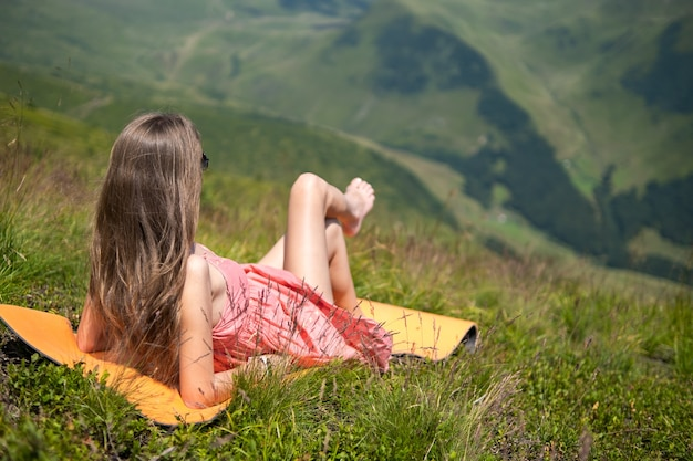Young woman in red dress lying down on green grassy field resting on a sunny day