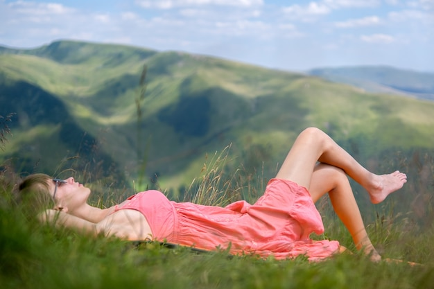 Young woman in red dress lying down on green grassy meadow on a warm sunny day in summer mountains enjoying view of nature.