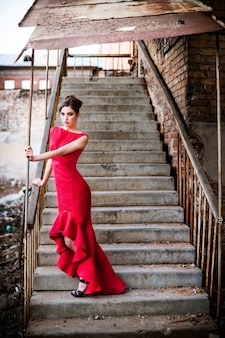 Young woman in red dress at old staircase