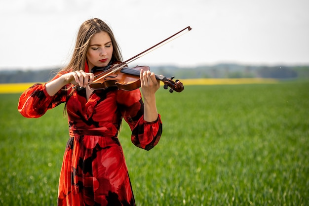 Young woman in red dress playing violin in green meadow
