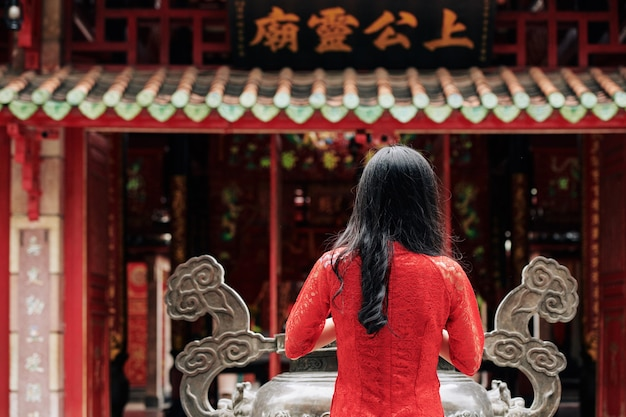 Young woman in red dress praying at urn with incense sticks at buddhist temple on spring festival, view from the back