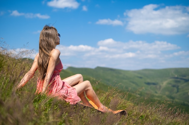 Young woman in red dress resting on green grassy field on a sunny day in summer mountains enjoying view of nature.
