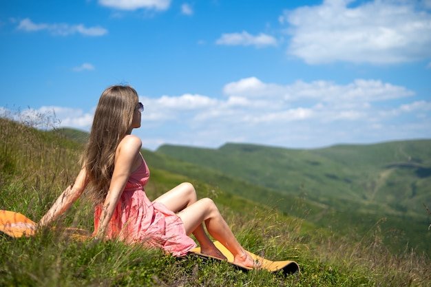 Young woman in red dress resting on green grassy field on a warm sunny day in summer mountains enjoying view of nature.