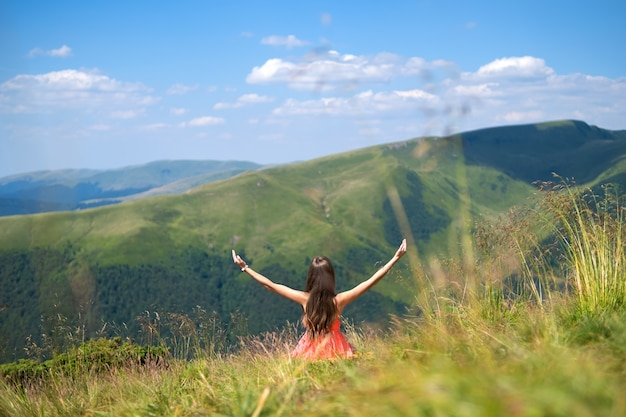 Young woman in red dress sitting on grassy meadow on a windy day in summer mountains raising up her hands enjoying view of nature.