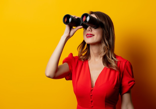 Young woman in red dress with binocular on yellow wall
