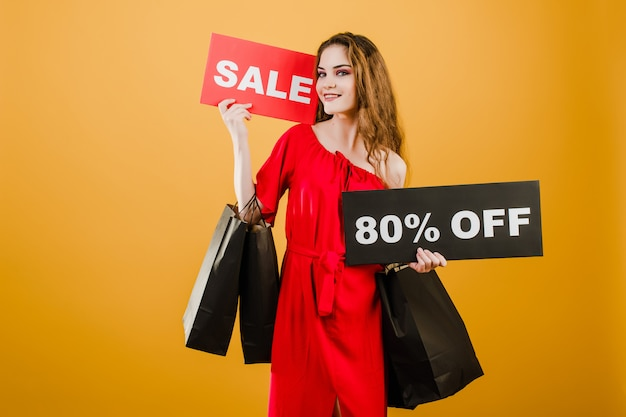 Young woman in red dress with sale 80% sign and paper shopping bags isolated over yellow