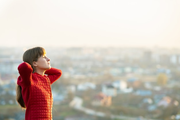 Young woman in red jacket standing with her hands behind head outdoors enjoying evening view. relaxing, freedom and wellness concept.