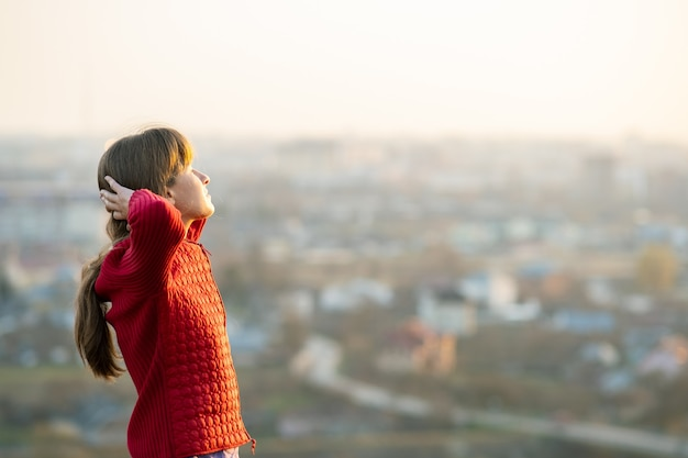 Young woman in red jacket standing with her hands behind head outdoors enjoying evening view.