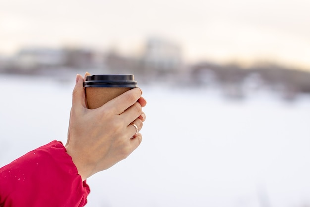 A young woman in a red jacket in winter holds a glass of hot coffee or tea
