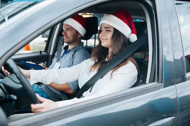 Young woman in red santa claus hat driving