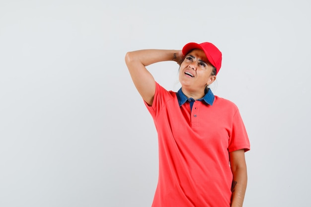 Young woman in red shirt and cap putting hand above head, thinking about something and looking pensive , front view.
