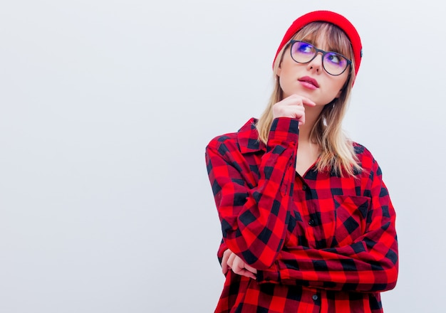 Young woman in red shirt and hat with glasses