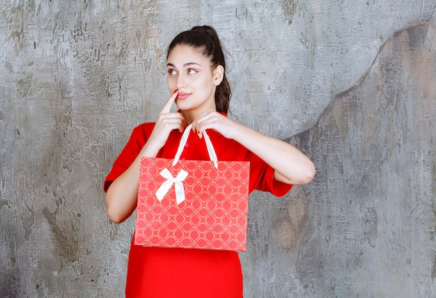 Young woman in red shirt holding a red shopping bag and looks confused and thoughtful.