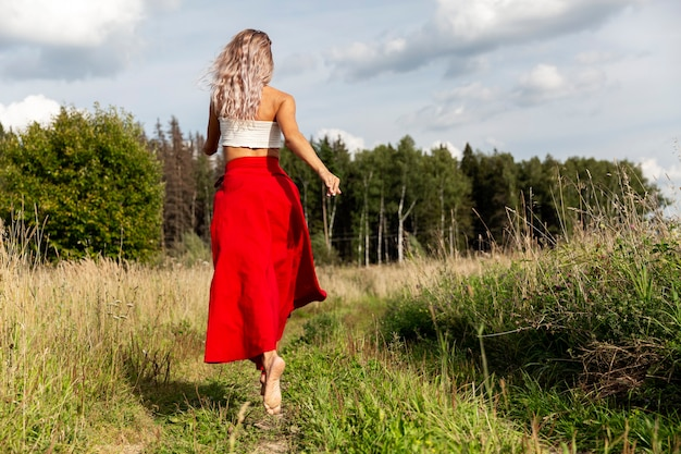 A young woman in a red skirt runs in the field
