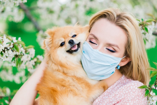 Young woman and red spitz with a medical mask on her face on nature on a spring day. coronavirus pandemic, quarantine.