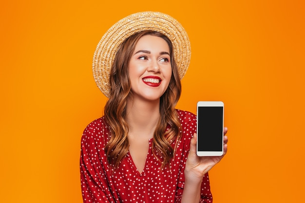 A young woman in a red summer dress straw hat holds a mobile phone and show it to the camera with empty black screen and looks at  mockup space for design orange wall