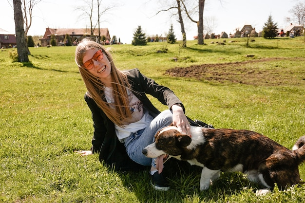 Young woman in red sunglasses plays with her corgi on a summer green lawn