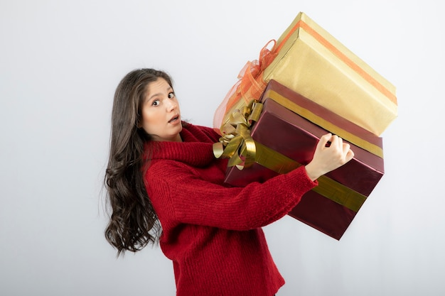 Young woman in red sweater carrying christmas presents .