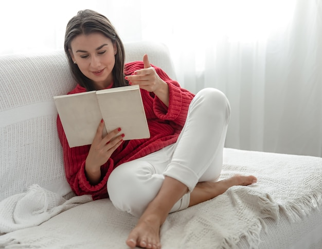 Young woman in a red sweater on the couch at home with a book in her hands.