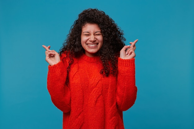 Young woman in red sweater, keeps arms up and fingers crossed