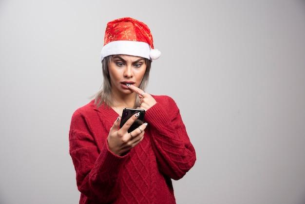 Giovane donna in maglione rosso guardando il cellulare su sfondo grigio.