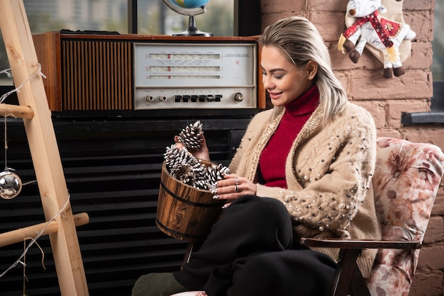 Young woman in red sweater looking at a wooden basket full of pinecones