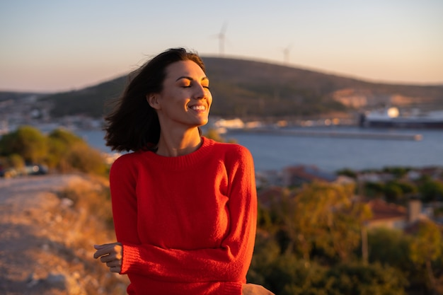 Young woman in a red sweater at a magnificent sunset on the mountain