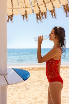 Young woman in a red swimsuit, drinking sparkling water from a transparent bottle on the beach