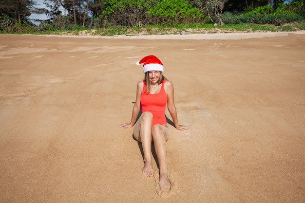 Young woman in red swimsuit and santa claus hat looking at camera