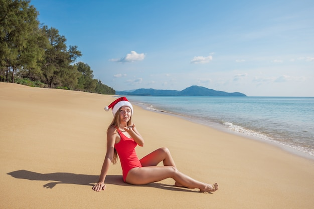 Young woman in red swimsuit and santa claus hat sending air kiss sitting on the empty beach