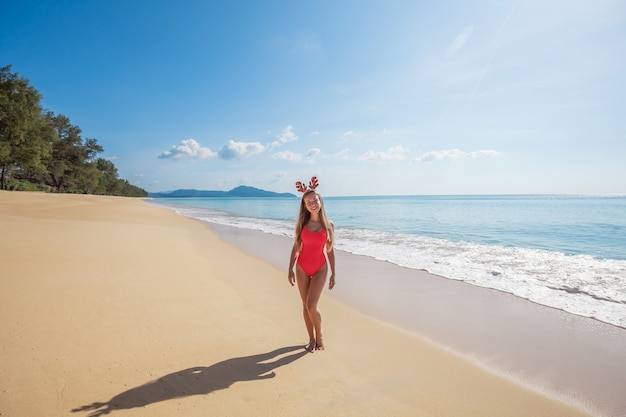 Young woman in red swimsuit wearing funny christmas reindeer antlers