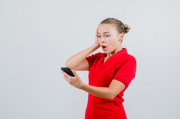 Giovane donna in maglietta rossa guardando il cellulare e guardando scioccata